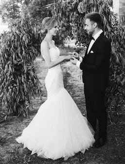 Пара в свадебном платье обменивается кольцами в саду с аркой. жених и невеста. черно-белое фото