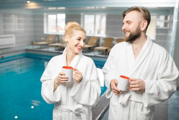 휴가 기간 동안 목욕 가운을 입은 커플이 분지 근처 스파에서 휴식을 취합니다.