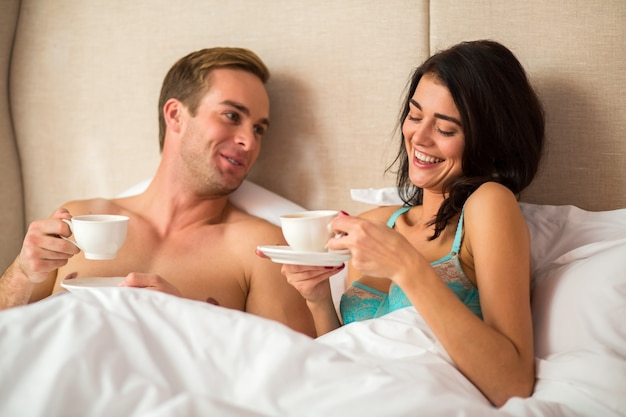 Пара в постели, держа чашки.