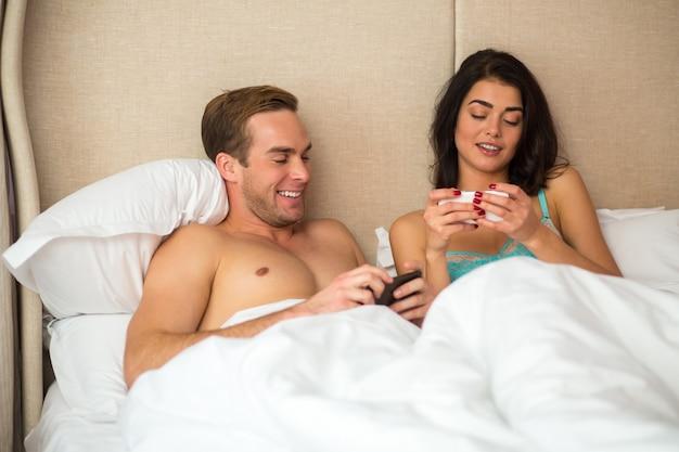 Пара в постели с телефонами.