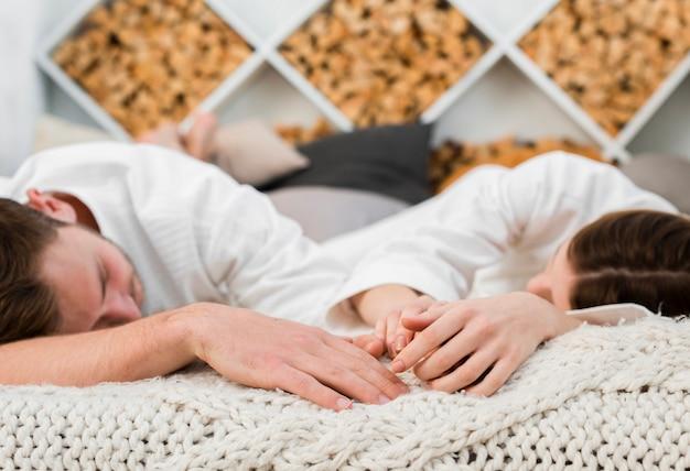 バスローブを着て寝ているベッドのカップル