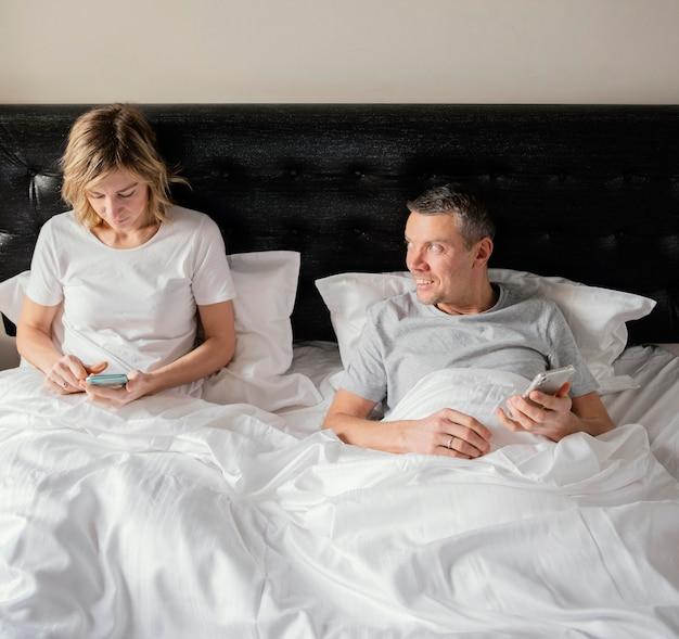 Пара в постели с помощью мобильных телефонов