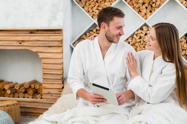 タブレットとバスローブが付いているベッドのカップル