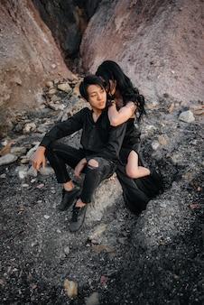 Пара в черной одежде позирует на природе