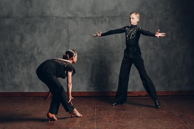 Пара в черных костюмах танцует в бальном танце румба.