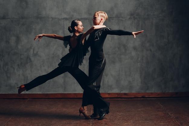 Пара в черном платье танцует бальные танцы румба.