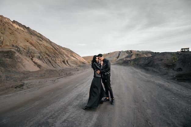 Пара в черной кожаной одежде позирует на природе