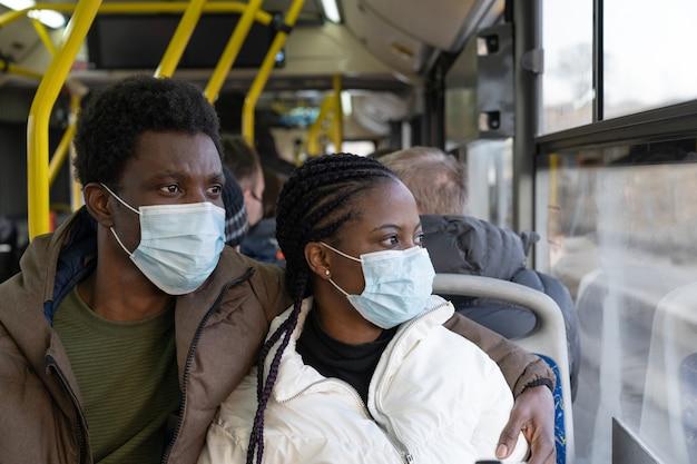 대중 교통에서 새로운 정상적인 아프리카 남자와 여자 여행하는 동안 마스크를 쓰고 버스에서 커플