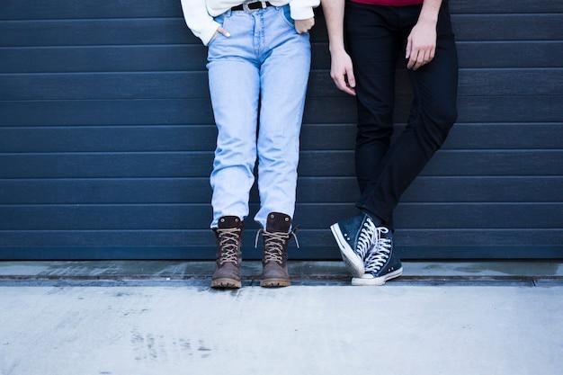 水色の壁に対して立っているカジュアルな服装のカップル
