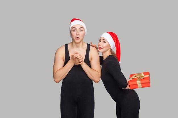 クリスマスの帽子のカップル。カメラを見てショックを受けた男。赤いギフトボックスを持って隠している女性と彼を驚かせたい。屋内、スタジオショット、灰色の背景で分離
