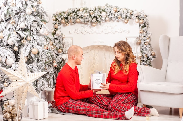 Пара в рождественском интерьере беременная женщина