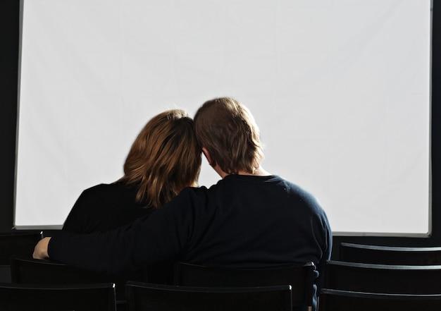 흰색 화면이 있는 영화관에서 커플