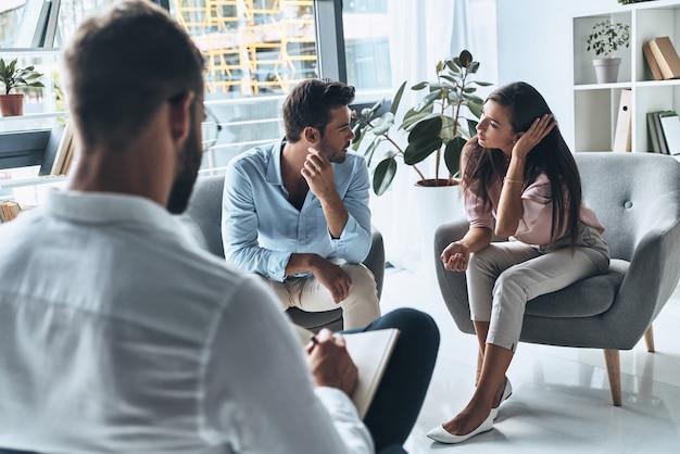 Пара в конфликте. молодая супружеская пара разговаривает, сидя на сеансе терапии
