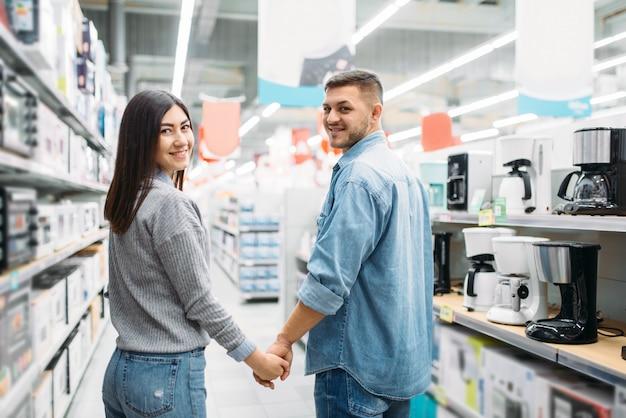 Пара в отделе бытовой техники, рынке. покупатели в магазине, семья выбирает товары народного потребления