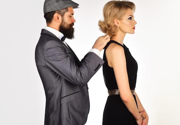 夕方の服を着たカップル。スタイリッシュな男性は女性のドレスアップを手伝います。