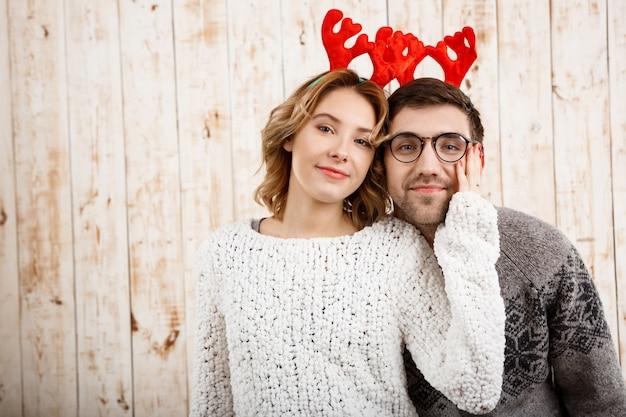 木製の壁に笑みを浮かべて偽の鹿の角のカップル
