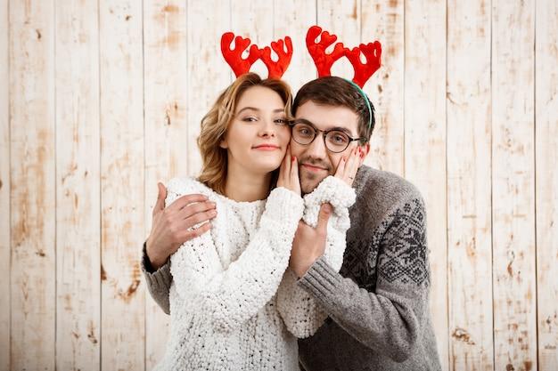 Пара в поддельных оленьих рогов, улыбаясь на деревянной стене