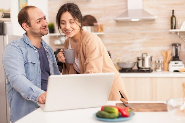 Пара перед ноутбуком в кухне улыбается. жена с чашкой кофе. мужчина и женщина-фрилансер. счастливая любящая веселая романтическая влюбленная пара дома с использованием современных беспроводных интернет-технологий wi-fi