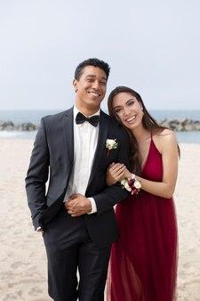 해변에서 졸업 파티 옷을 입은 커플