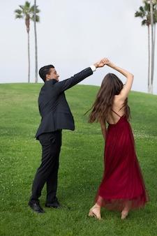 Пара в выпускной одежде выпускного вечера на открытом воздухе
