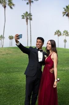 Пара в выпускной одежде выпускного вечера, делающая селфи