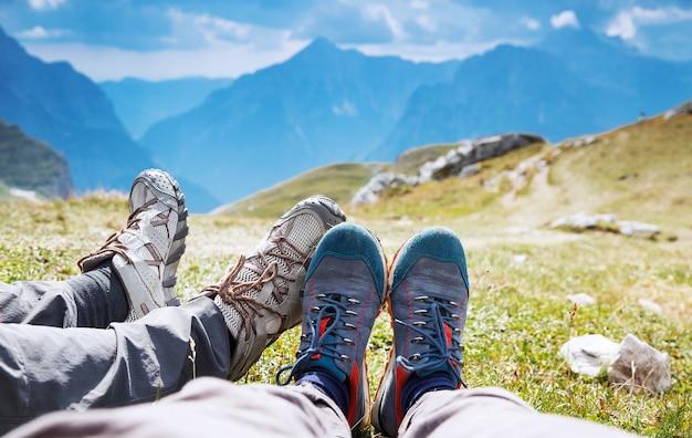 山の背景にハイキングブーツのカップル山でのトレッキングの日に家族