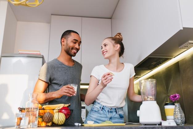 幸せそうな顔で話している台所で家の服のカップル。ペアでチャットしながら食事を作ります。暖かい関係、健康的な食事、笑顔。