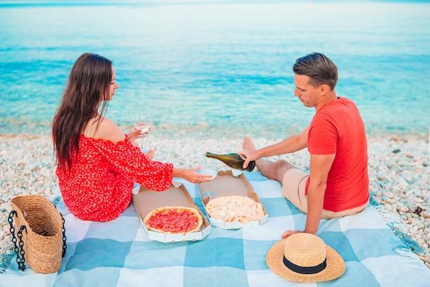 新婚旅行のカップルはビーチでピクニックをします