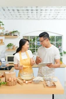 インターネットでレシピを見ている台所のカップル