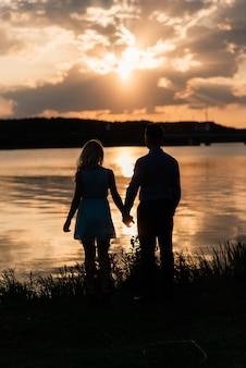 ロマンチックな湖オレンジ色の夕日で愛のバックライトのシルエットのカップル。