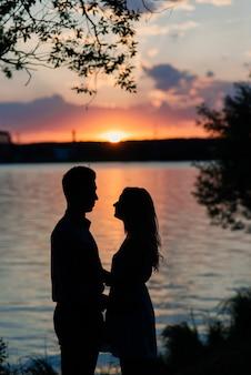 オレンジ色の湖の夕日で愛バックライトシルエットのカップル