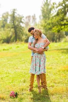 Влюбленная пара красивых молодых людей, обнимающихся в летнем парке в солнечный день.