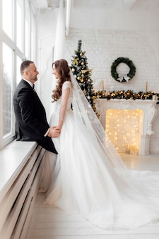 Влюбленная пара жених и невеста позирует в студии на фоне, украшенном елкой