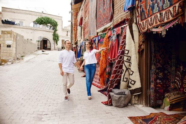 愛するカップルは、トルコの東洋市場でカーペットと手作りのテキスタイルを購入します。男性と女性の抱擁と陽気な幸せそうな顔