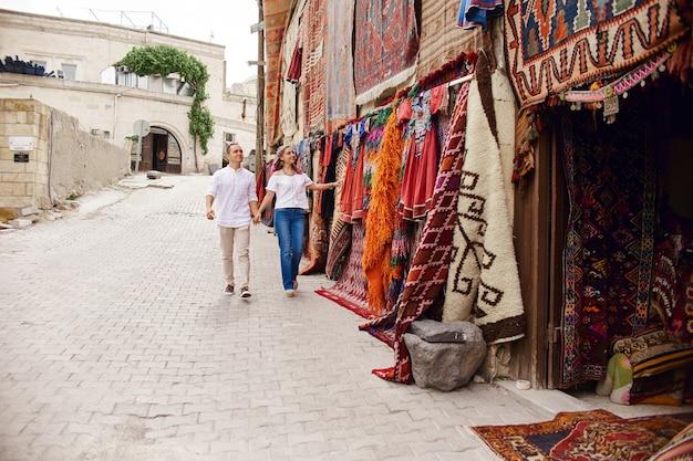 사랑에 빠진 부부는 터키의 동양 시장에서 카펫과 수제 직물을 구입합니다. 남녀의 포옹과 쾌활한 행복한 얼굴