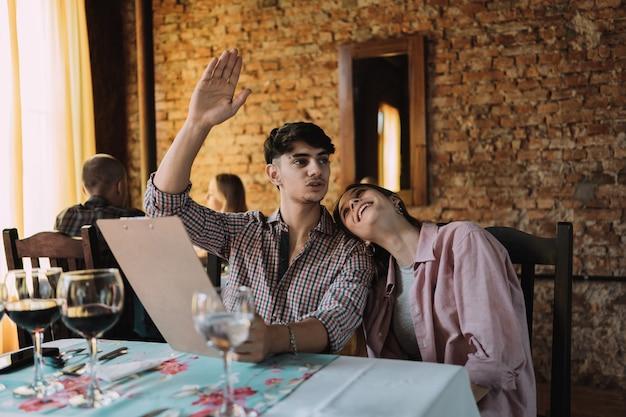 Влюбленная пара звонит официанту в ресторане