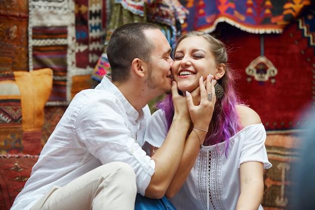 Влюбленная пара выбирает на рынке турецкий ковер. веселые радостные эмоции на лице мужчины и женщины. день святого валентина в турции
