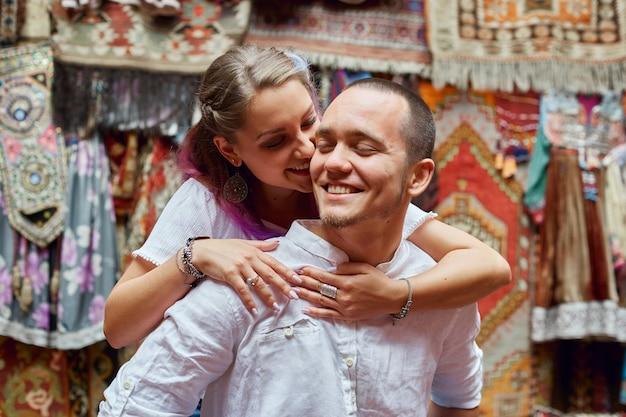 사랑에 빠진 부부는 시장에서 터키 카펫을 선택합니다. 남자와 여자의 얼굴에 쾌활한 즐거운 감정. 터키의 발렌타인 데이