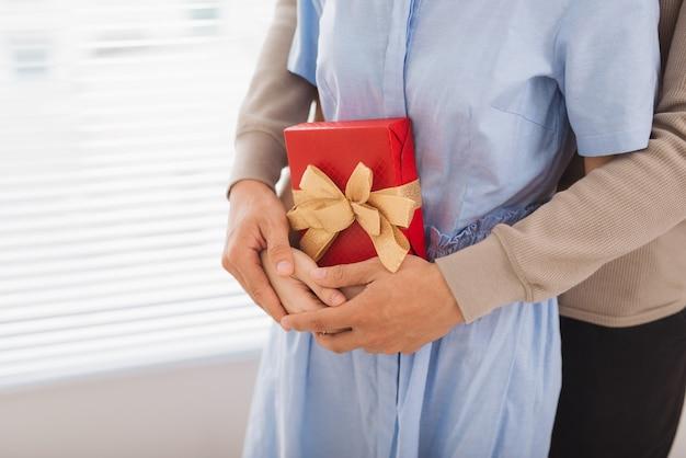 恋をしているカップル。包まれたプレゼントで抱き締めるカップル