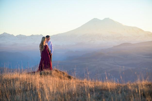愛のカップルは、夕暮れ時の山での旅行を受け入れます。夕暮れ時の赤いドレスの女の子