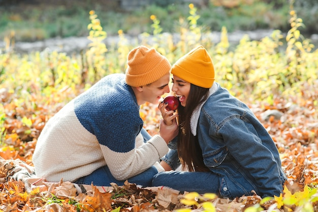 秋を楽しむ恋のカップル。自然の中を散歩するファッショナブルなカップル。愛、反逆、ライフスタイル。秋の気分、休暇。公園で一緒に休んでいる女性と男性。