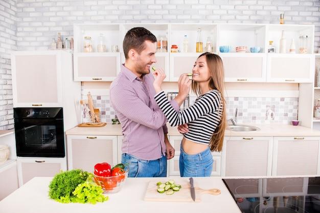 キッチンでキュウリを食べ合う恋愛カップル