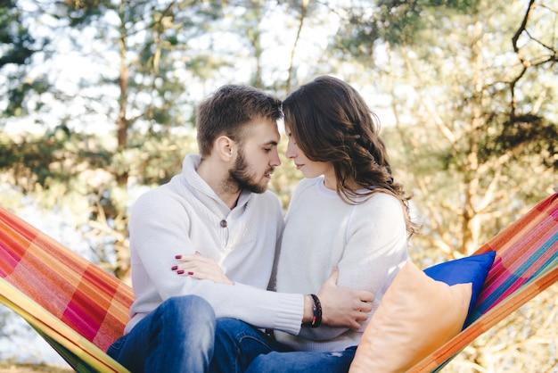 Влюбленная пара, девушка и парень в гамаке наслаждаются в лесу