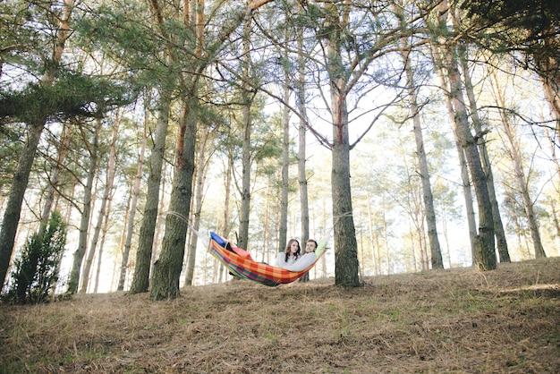 愛のカップル、ハンモックの女の子と男は森の中で楽しんで、旅行のラブストーリーのコンセプト