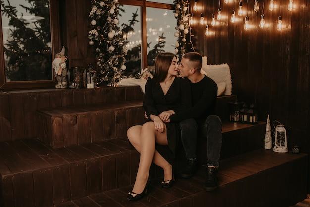 Влюбленная пара парень и девушка обнимаются, целуются возле елки у окна на деревянном подоконнике