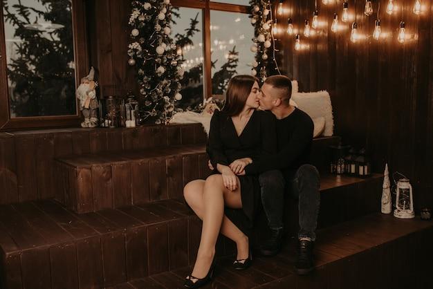 Влюбленная пара парень и девушка обнимаются, целуются у окна на деревянном подоконнике