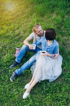 愛のカップルは、夏のリンゴ園で休憩します