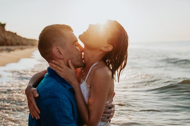 Влюбленная пара веселится и купается в морской воде на берегу на рассвете