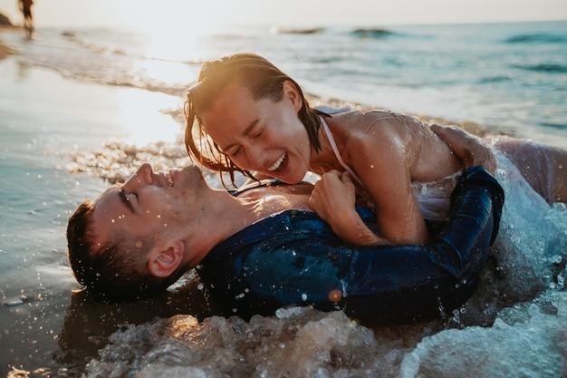 Влюбленная пара веселится и купается в морской воде на берегу на рассвете Premium Фотографии