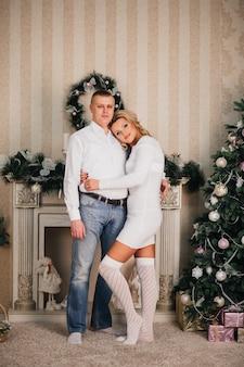 愛のカップルは、クリスマスツリーの背景に抱き締める